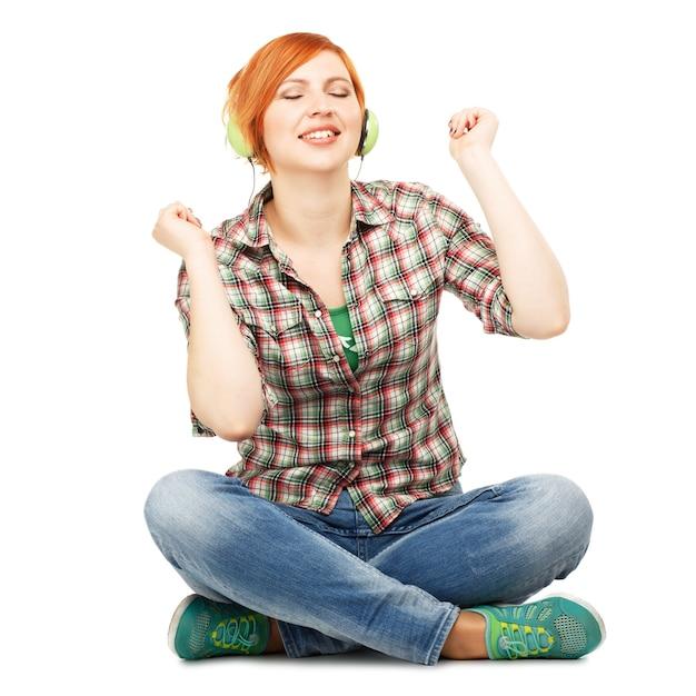 Jong meisje genieten van het luisteren naar muziek op koptelefoon geïsoleerd op wit Premium Foto