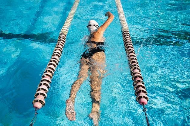 Jong meisje genieten van zwemmen bij het zwembad Premium Foto