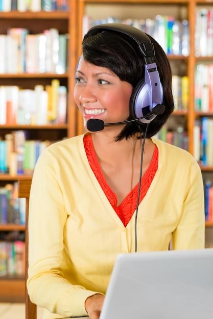 Jong meisje in bibliotheek met laptop en hoofdtelefoons Premium Foto