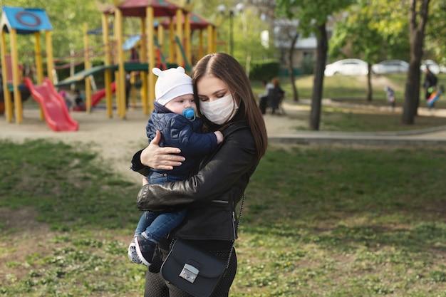 Jong meisje in een beschermend masker, knuffels haar kleine kind. covid-19 Premium Foto