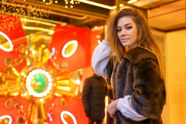 Jong meisje in een bontjas poseren voor de camera feestelijke sfeer Premium Foto