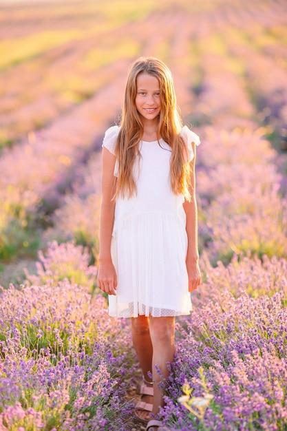 Jong meisje in een veld van lavendelbloemen Premium Foto