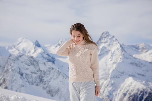 Jong meisje in een winter pak kijken naar de bergen Premium Foto
