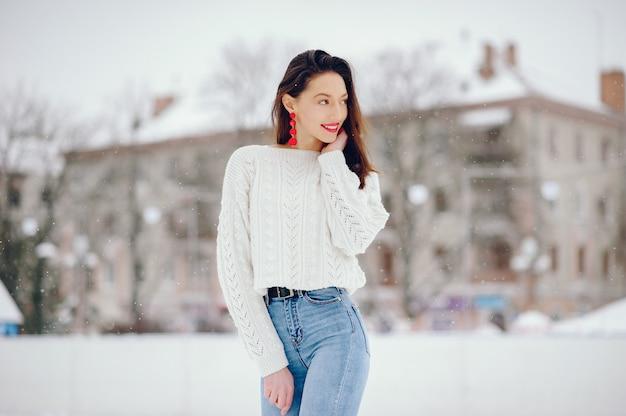 Jong meisje in een witte sweater die zich in een de winterpark bevindt Gratis Foto