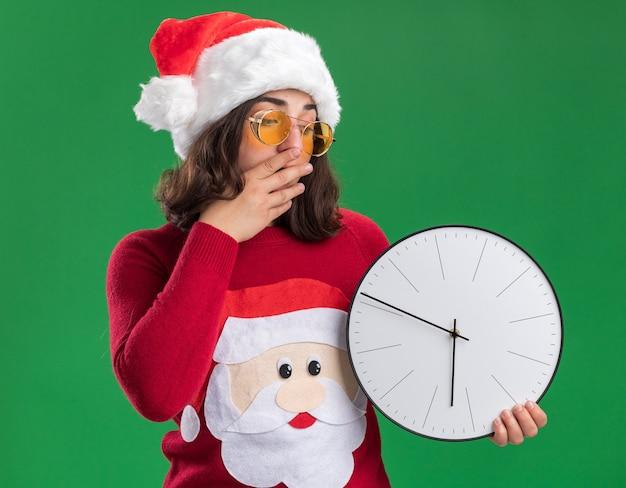 Jong meisje in kerst trui dragen kerstmuts en bril houden muurklok kijken verbaasd en verbaasd bedekkende mond met hand staande over groene achtergrond Gratis Foto