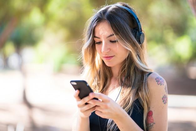 Jong meisje in openlucht in een park dat aan muziek met mobiel luistert Premium Foto