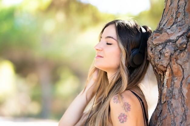 Jong meisje in openlucht in park het luisteren muziek Premium Foto