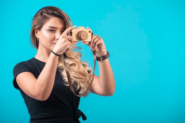 Jong meisje in zwart shirt hing een speelgoedcamera aan haar nek en nam een foto. Gratis Foto