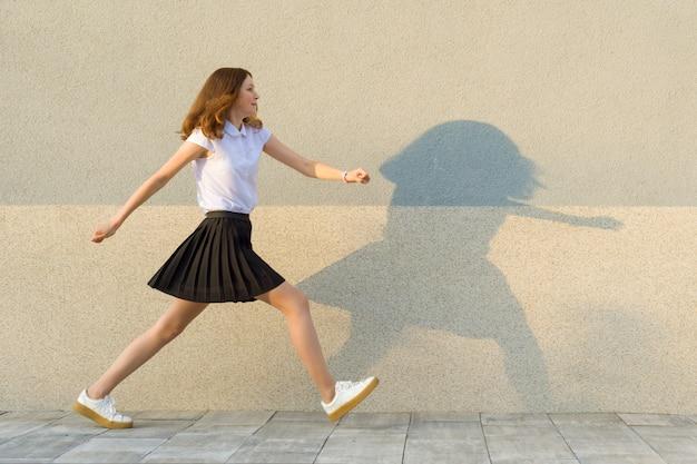 Jong meisje loopt langs de grijze muur Premium Foto
