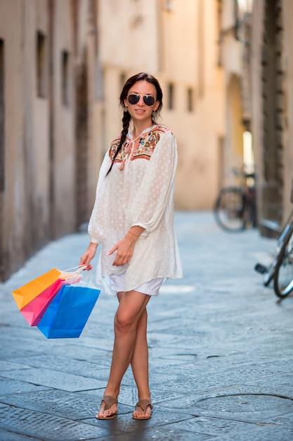 Jong meisje met boodschappentassen op smalle straat in europa. portret van het mooie gelukkige vrouwenholding het winkelen zakken glimlachen Premium Foto