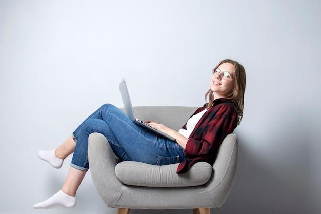 Jong meisje met een laptop zittend op een zachte comfortabele stoel, en smilling, een vrouw met behulp van een computer tegen een witte blinde muur, ze freelancen en afdrukken van tekst, kopie ruimte Premium Foto