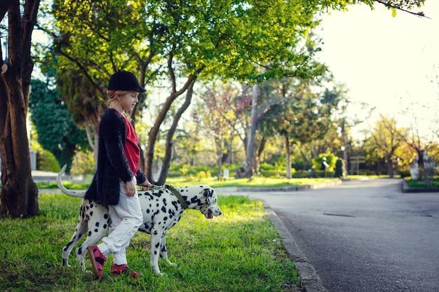 Jong meisje met haar dalmatische honden in een de lentepark. zonsondergangtijd, rood, wit en zwart Premium Foto