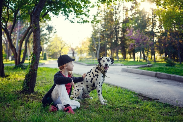 Jong meisje met haar dalmatische honden in een de lentepark. Premium Foto