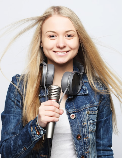 Jong meisje met microfoon zingen Premium Foto