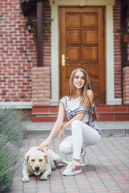 Jong meisje met retriever op gang voor het huis. aantrekkelijke lachende vrouw labrador retriever aaien en kijken naar de camera. Premium Foto