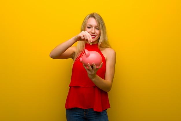 Jong meisje met rode kleding over gele muur die een spaarvarken neemt en gelukkig omdat het hoogtepunt is Premium Foto