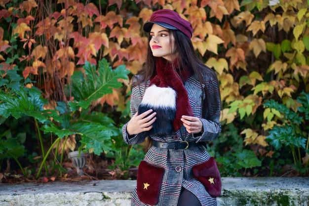 Jong meisje met zeer lang haar die en de winterlaag en glb op de achtergrond van de herfstbladeren glimlachen dragen Premium Foto