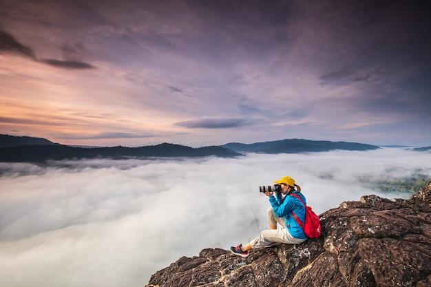 Jong meisje neemt foto's de zee van mist op hoge berg. Premium Foto