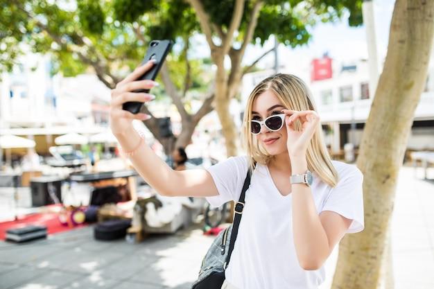 Jong meisje nemen selfie uit handen met telefoon op zomer stad straat. Gratis Foto
