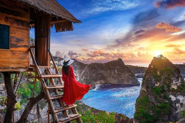 Jong meisje op trappen van huis op boom bij zonsopgang in het eiland nusa penida, bali in indonesië Gratis Foto
