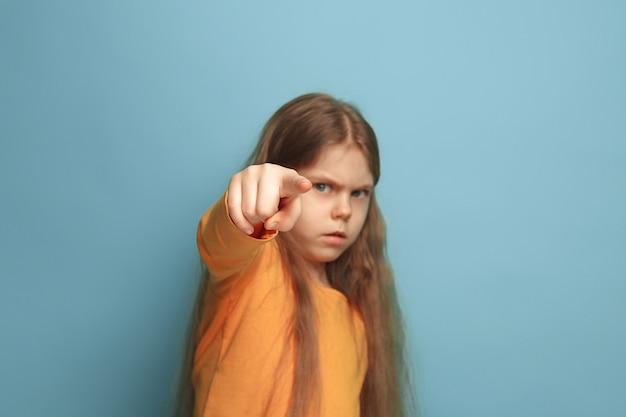 Jong meisje poseren en wijzen naar de voorkant tegen blauwe muur Gratis Foto