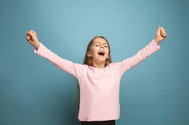 Jong meisje poseren tegen blauwe muur Gratis Foto