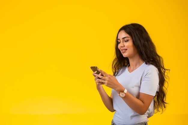 Jong meisje praten en chatten op haar telefoon tijdens het glimlachen Gratis Foto