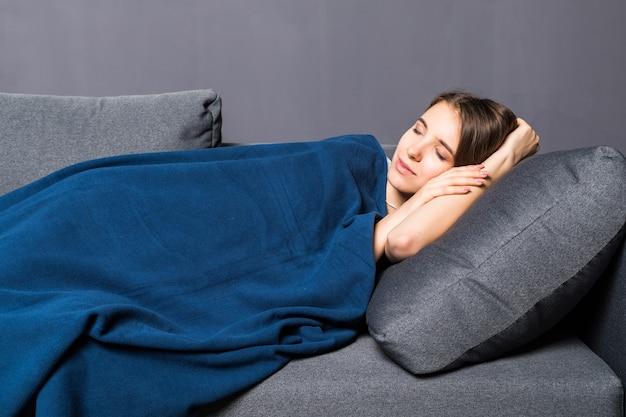 Jong meisje slapen op een bank bedekt met blauwe sprei op grijze achtergrond Gratis Foto