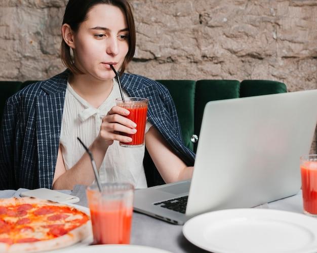 Jong meisje smoothie drinken en werken op de laptop Gratis Foto