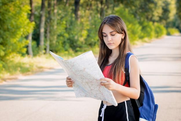 Jong meisje verdwaalde op het platteland terwijl ze alleen reisde en probeert een richting te vinden met een papieren kaart Premium Foto