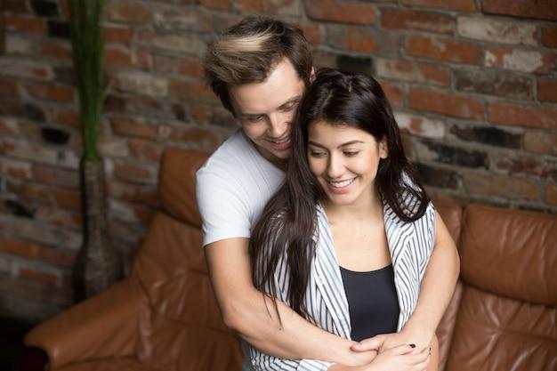 Jong millennial paar thuis omhelzen, gelukkig over eerste zwangerschap Gratis Foto
