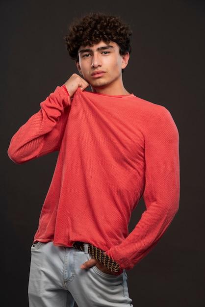 Jong model in het rode overhemd stellen door handen op zijn hals te leggen. Gratis Foto