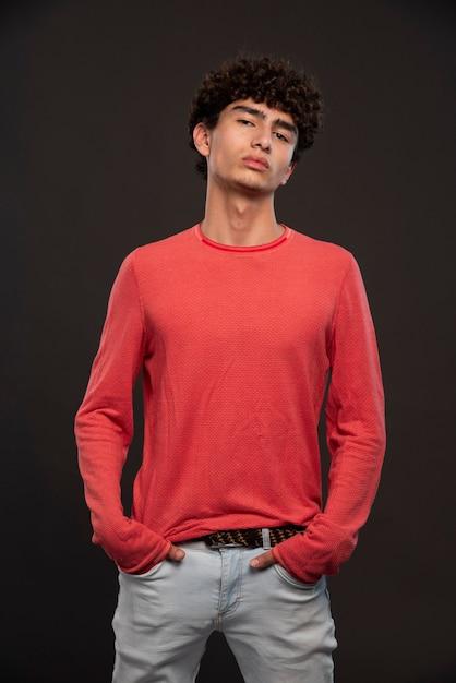 Jong model in het rode overhemd stellen door handen op zijn zakken te leggen. Gratis Foto