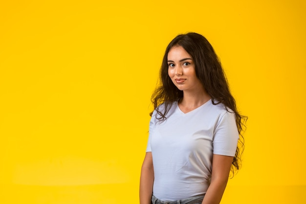 Jong model poseren bij gele muur en glimlachen. Gratis Foto