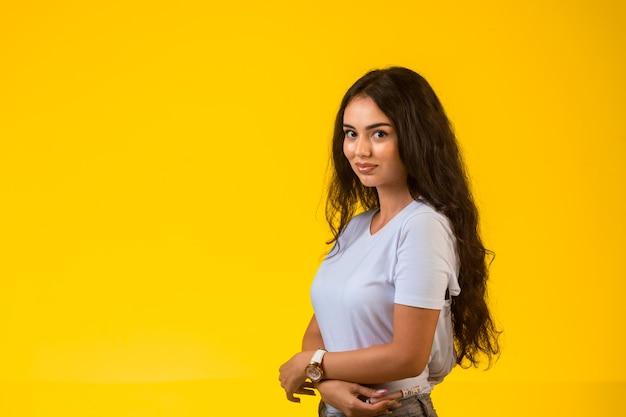 Jong model poseren bij gele muur. Gratis Foto