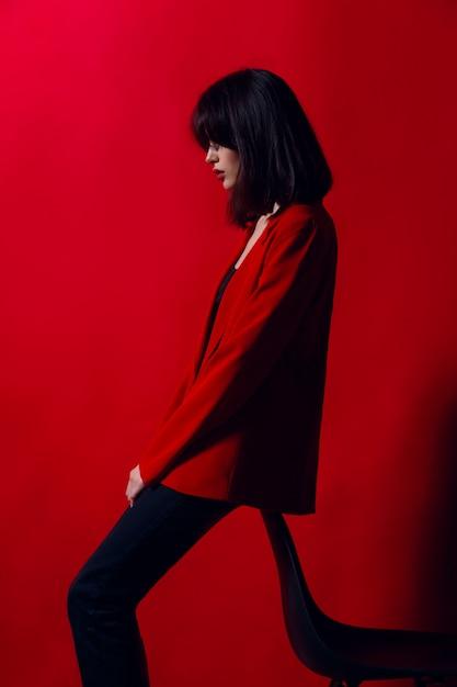 Jong model poseren in modieuze rode pak en zwarte broek, geïsoleerd op een rode achtergrond. Premium Foto