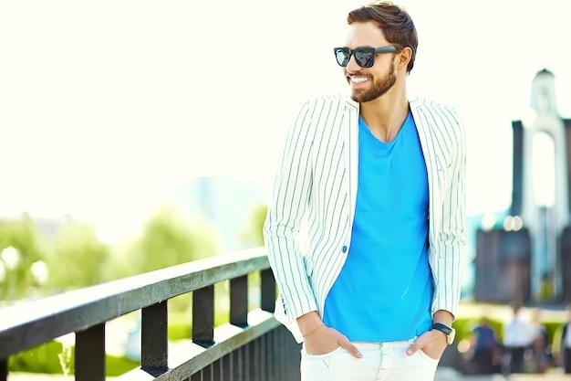 Jong modieus zeker gelukkig knap zakenmanmodel die in kostuum hipster kleren in de straat in zonnebril lopen Gratis Foto