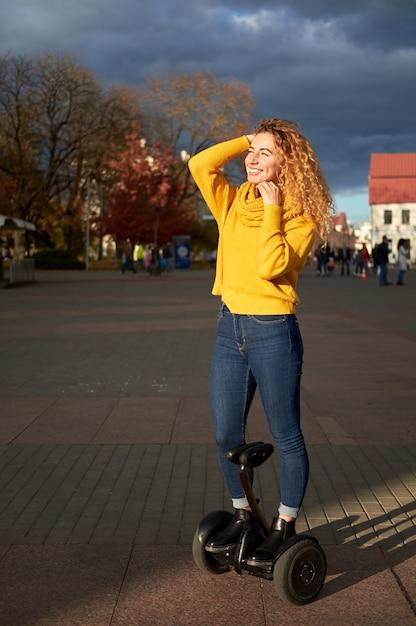 Jong mooi atletisch geschikt meisje die op hoverboard in de straat berijden Premium Foto