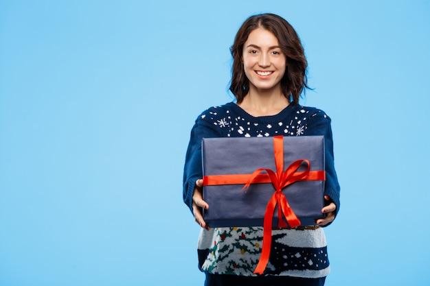Jong mooi donkerbruin meisje in het comfortabele gebreide sweater het glimlachen doos van de holdingsgift over blauwe achtergrond. Gratis Foto