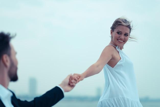 Jong mooi echtpaar die op het jacht op vakantie omhelzen Premium Foto