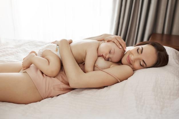 Jong mooi gelukkig mamma die het koesteren van haar baby de borst geven die thuis op bed liggen Gratis Foto