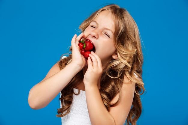 Jong mooi meisje dat aardbei over blauwe muur eet Gratis Foto