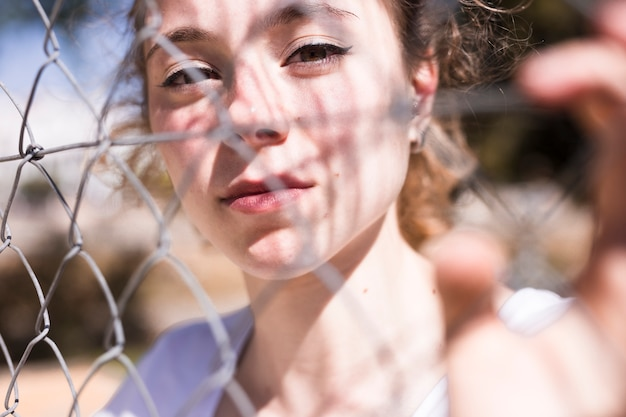 Jong mooi meisje dat door metaalnet kijkt Gratis Foto