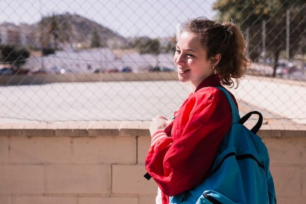 Jong mooi meisje dat zich dichtbij sportsground bevindt Gratis Foto