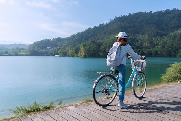 Jong mooi meisje die een fiets berijden op fietspad bij het meer in de ochtend. actieve mensen. buitenshuis Premium Foto