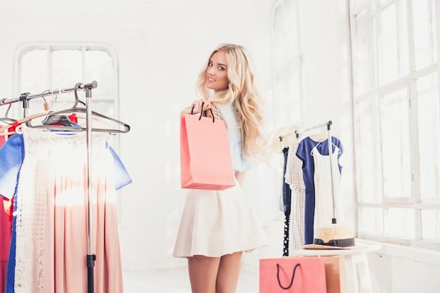 Jong mooi meisje die en op kleding bij winkel kiezen proberen Gratis Foto