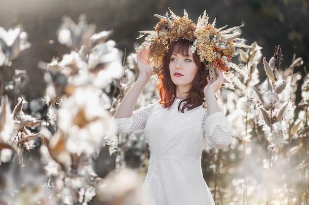Jong mooi meisje in een witte vintage jurk en een krans van gedroogde bloemen op het hoofd in een herfst veld Premium Foto