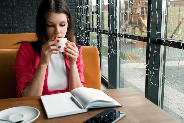 Jong mooi meisje, onderneemster het drinken thee of koffiezitting in koffie Premium Foto