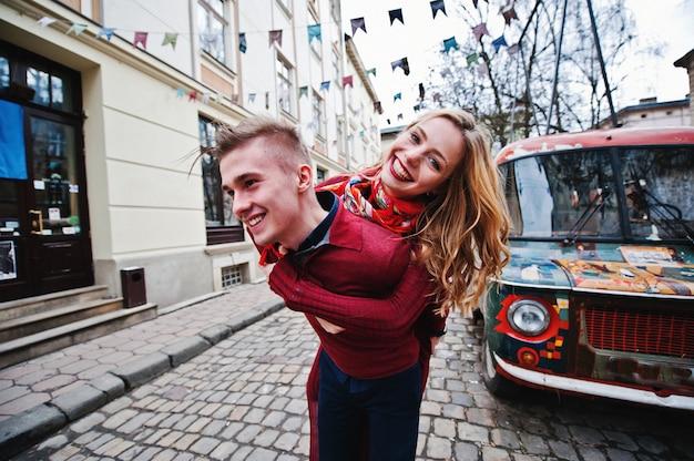Jong mooi modieus manierpaar in een rode kleding in liefdesverhaal bij de oude stad, die pret oude retro uitstekende bus hebben als achtergrond Premium Foto