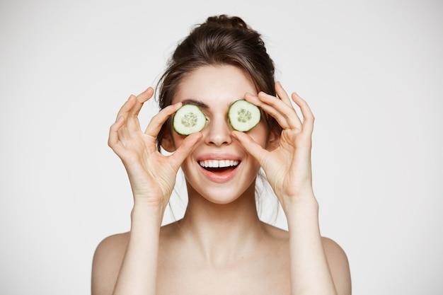 Jong mooi naakt meisje die verbergende ogen achter komkommerplakken glimlachen over witte achtergrond. schoonheid huidverzorging en cosmetologie. Gratis Foto